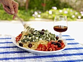 Spaghetti with spinach & feta, garnished with tomato salad