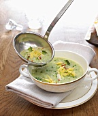 Broccoli soup in bowl and ladle