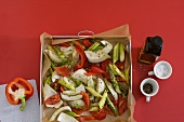Vegetables on a baking tray lined with baking parchment