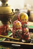 Matryoshka dolls, samovar and glasses in background