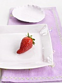 A strawberry on a white china plate