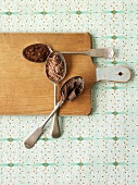 3 spoons with cocoa powder, grated chocolate & chocolate curls