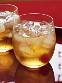Ginger Ale with cocktail cherry and ice cubes