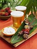 Grilled lamb kebabs on banana leaf, yoghurt dip and beer