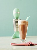 A glass of chocolate milkshake, liquidiser in background