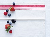 Strawberries, blueberries and blackberries on tea towel