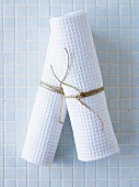 Rolled-up towels on pale blue tiles