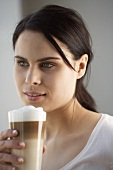 Young woman with a glass of latte macchiato