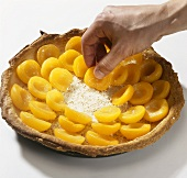 Filling a puff pastry tart case with apricots