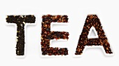 Getrocknete Teeblätter in Schälchen mit Schriftzug TEA
