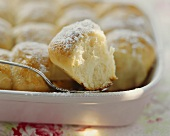 Buchteln (yeast dumplings) with icing sugar in baking dish
