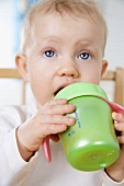 Small child drinking out of a training cup