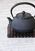 Asian cast-iron teapot on wooden stand