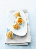 Physalis on white plate and on blue and grey napkin