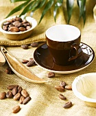 Brown cup & saucer on jute with cocoa beans & palm leaf