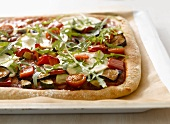 Vegetable pizza on baking tray lined with baking parchment