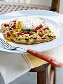 Pizza mit Artischockencreme und pochiertem Ei belegt