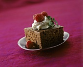 A piece of chocolate cake with cream and raspberries