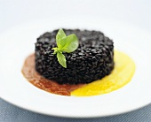 Black rice pudding on fruit sauce