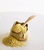 Bulgur on wooden spoon and in small sack