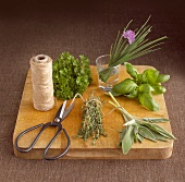 Fresh herbs, scissors and kitchen string on wooden board