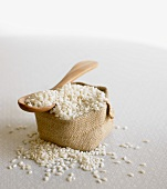 Arborio rice (risotto rice) on wooden spoon & in small sack