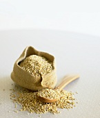 Kibbled oats on wooden spoon and in small sack