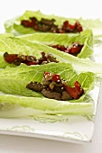 Beef with sesame seeds, ginger & peppers on lettuce leaves