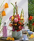Arrangement of gladioli & dahlias on table laid for coffee