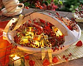 Rose hips and Chinese lanterns in basket with windlights