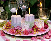 Candles, windlights and flowers on plate