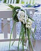 White lilac and grasses on the back of a chair