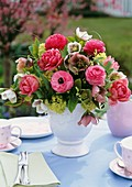 Vase of ranunculus, Lenten roses and viburnum