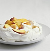 Pavlova with peach slices and cream