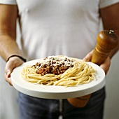 Man holding plate of spaghetti bolognese and pepper mill