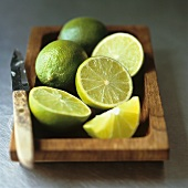 Limes with knife in a wooden dish