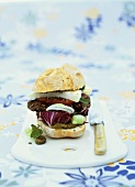 Grain and olive burger in bun with pesto and feta cheese