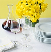 Red wine, glasses, pile of plates, vase of daffodils