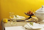 Laid table with soup tureen and fresh pears