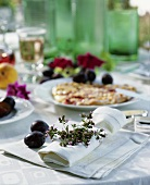 Napkin decorated with herbs & plums, plum flat cake behind