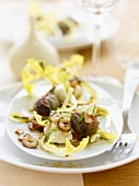 Dandelion salad with bacon-wrapped prunes and hazelnuts