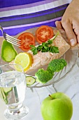 Salmon fillet with vegetables, a glass of water & an apple