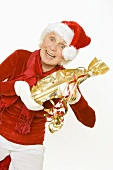 Elderly lady in Father Christmas hat holding a gift