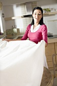 Woman putting tablecloth on table