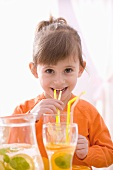 Little girl drinking lemonade through a straw