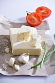 Feta (sheep's cheese), garlic and tomato on paper