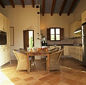 Kitchen with dining table and rattan armchairs