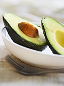 Halved avocado with stone in a dish