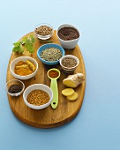 Various spices in small dishes on a wooden board