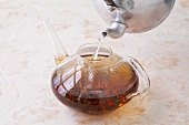 Pouring hot water over tea leaves
